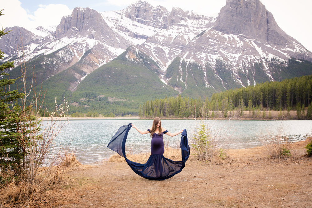 Gorgeous blue gown on a mother-to-be. Maternity session in the mountains in Canmore, Alberta. Canmore maternity photographer. Milashka Photography