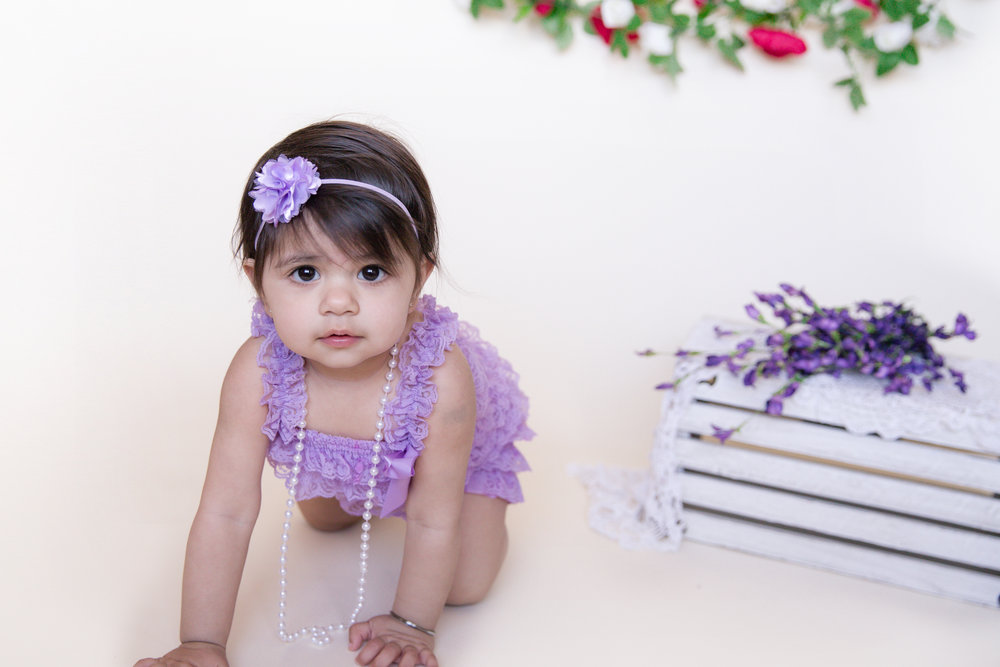 Little girl dressed in a purple romper crawling. Calgary children photographer. Milashka Photography.