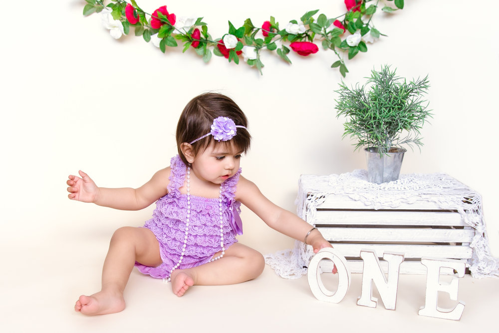 Sweet little girl dressed in a purple romper. 1st Birthday photoshoot ideas. Calgary children photographer. Milashka Photography.
