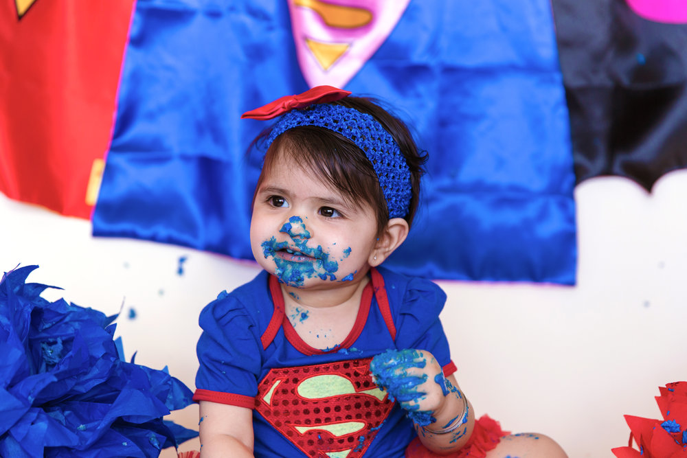 Happy girl covered in cake. Superhero inspired cakesmash photoshoot. Calgary cakesmash photographer.