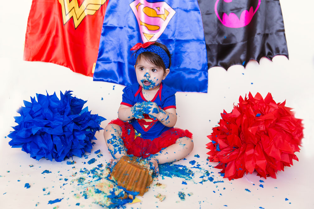 Smashing that cake till there is not a crumb left. Superhero inspired cakesmash photoshoot for girls. Milashka Photography - Calgary cakesmash photographer.