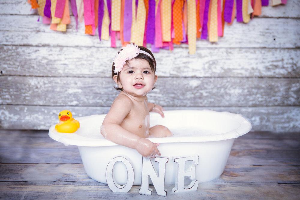 Baby girl enjoying her bubble bath. First birthday. Cakesmash. Bubble bath. Calgary photographer. Milashka Photography