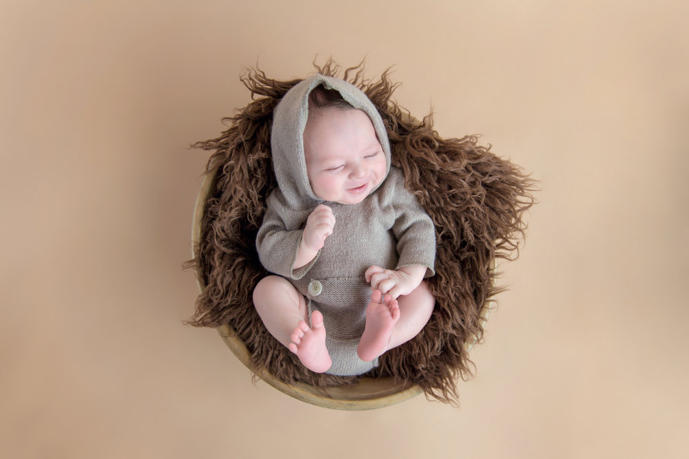 Newborn baby boy smiling in a bowl. Calgary newborn photographer. Milashka Photography.