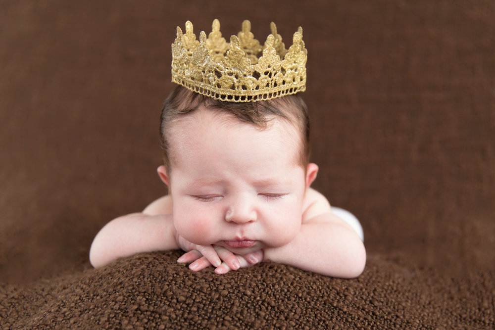 Newborn baby boy wearing a crown on a beanbag. Calgary Newborn Photographer. Milashka Photography