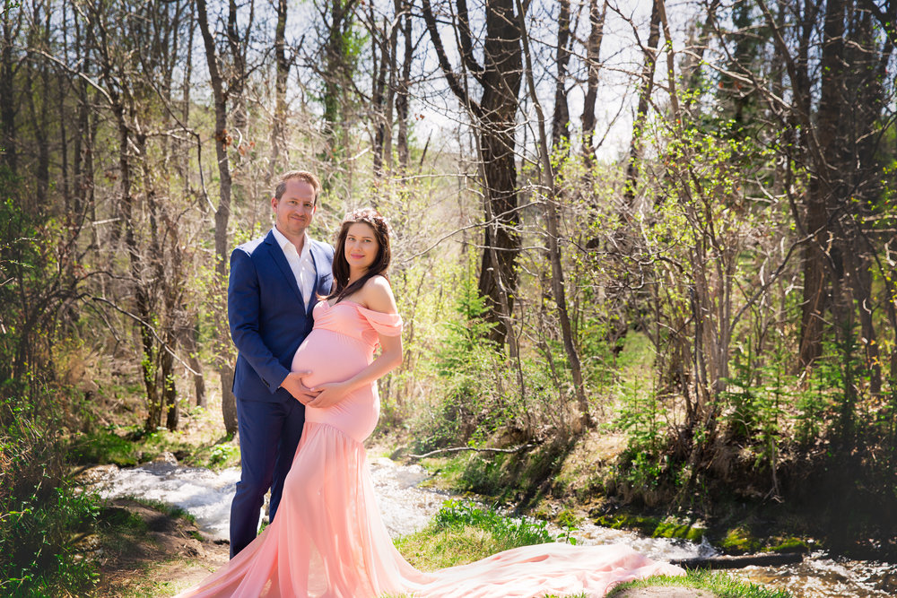 Parents-to-be by the water. Mom is wearing a beautiful pink gown. Calgary Maternity Photographer. Milashka Photography