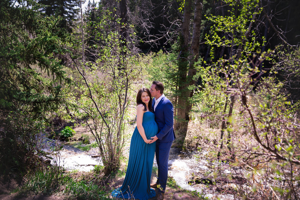 Parents-to-be by the water in a forest. Mom-to-be is wearing a blue gown. Calgary Maternity Photographer. Milashka Photography