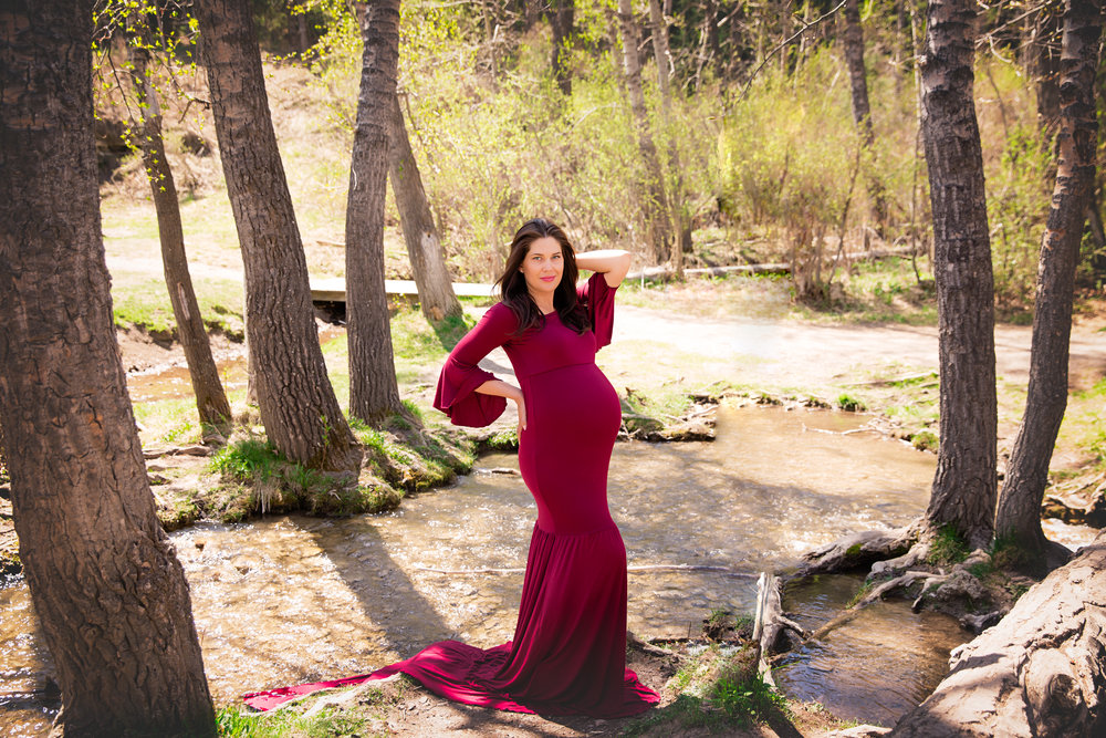 Lady in Red. Gorgeous mother-to-be by the water in a forest wearing red gown. Calgary Maternity Photographer. Milashka Photography