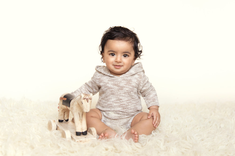 Baby boy sitting on a flokati rug with a wooden antique horse and smiling. Calgary baby photographer. Milashka Photography