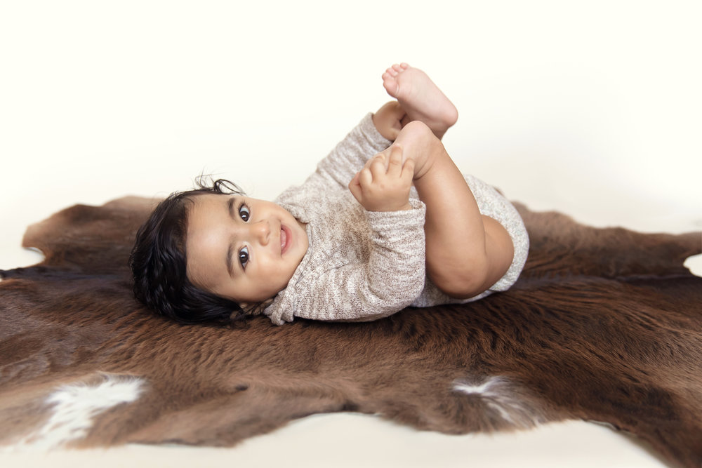 Baby boy lying on a rug, holding his feet and smiling. Calgary baby photographer. Milashka Photography