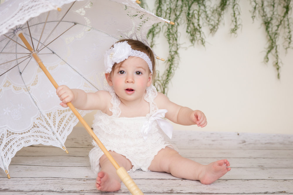 Baby girl wearing cute white romper, sitting on a floor holding on to an umbrella. Calgary baby photographer. Milashka Photography