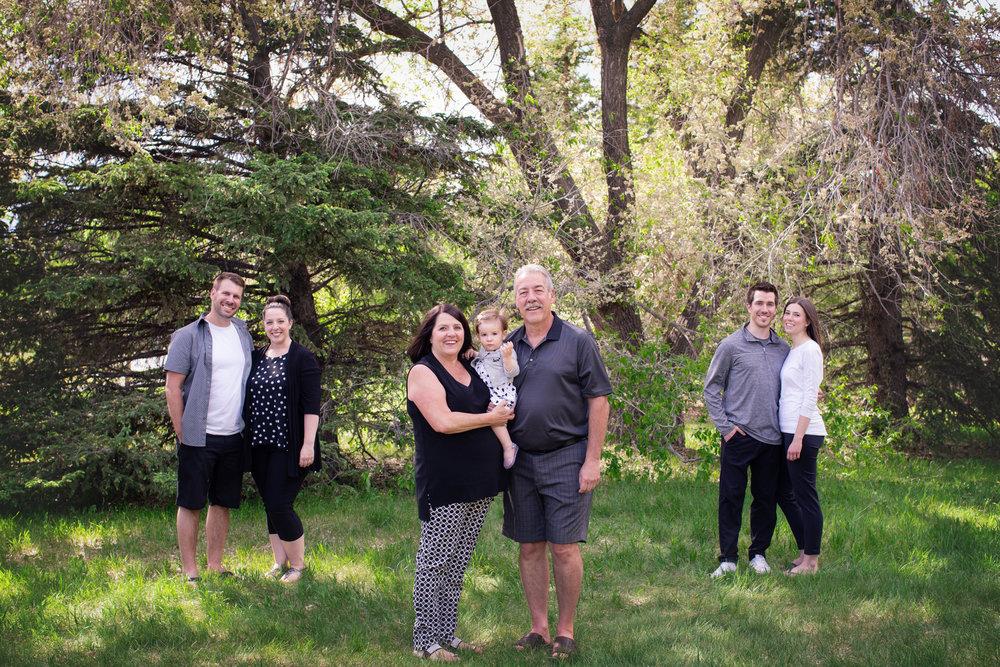 Family separated by inner families. Grandparents holding their granddaughter and other two couples are on each side. Alberta family photographer. Milashka Photography