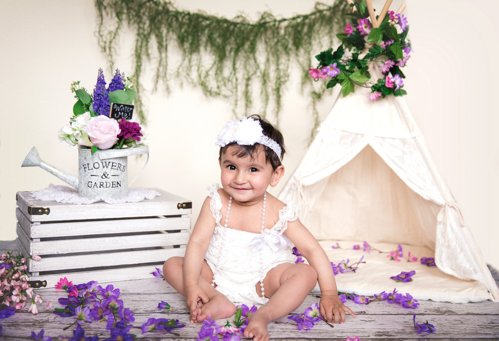 Birthday girl is sitting in front of a cute white tipi surrounded with flowers. 1st birthday set up photoshoot ideas. Calgary baby photographer. Milashka Photography