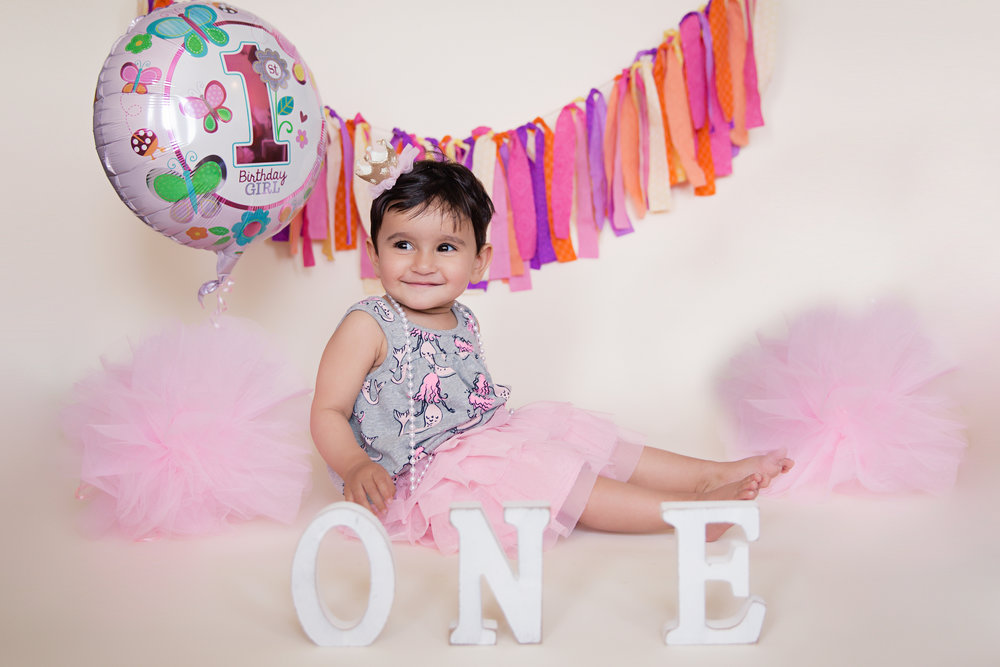 Little girl is turning one. Balloon, ONE letters, pompoms decorations. First Birthday photoshoot ideas. Calgary Photographer. Milashka Photography
