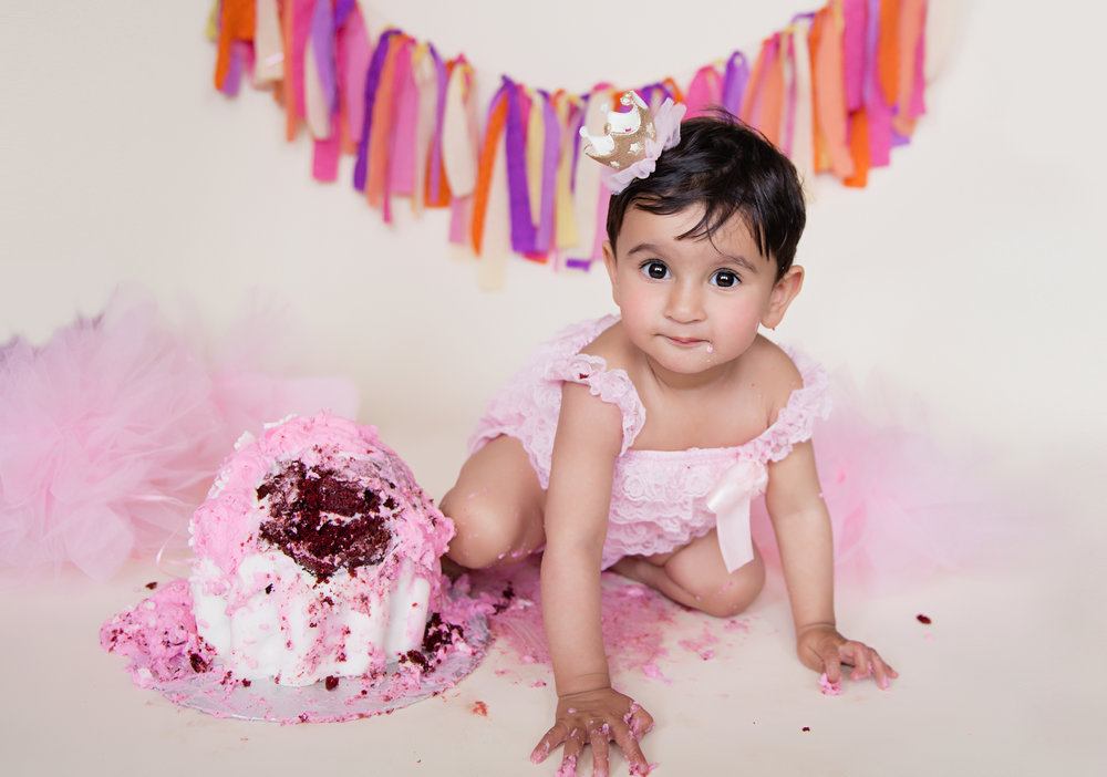 Baby is crawling away from a smashed cake. Calgary cakesmash photographer. Milashka Photography.