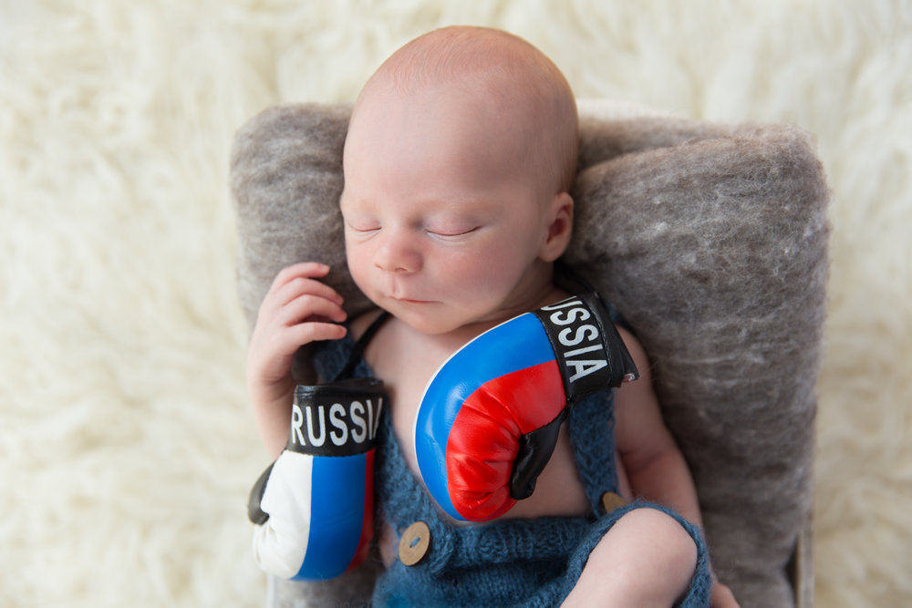 Russian Inspired Newborn Photoshoot. Baby boy wearing a blue overall and Russian boxer gloves. Calgary Newborn Photographer. Russian Newborn Photographer. Milashka Photography