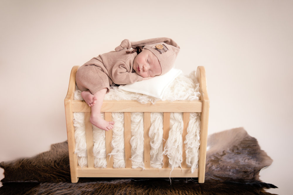 Newborn baby boy on top of a bed. Calgary and Airdrie newborn photographer. Milashka photography