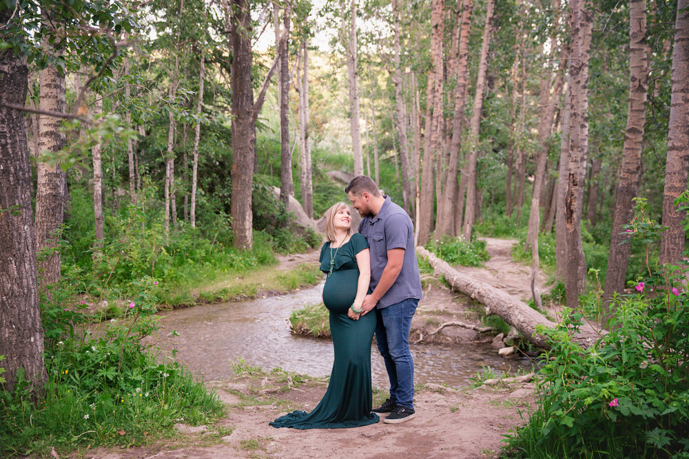 Expecting couple in a forest. Mom-to-be is wearing a beautiful green gown. Milashka Photography - Calgary's maternity photographer.