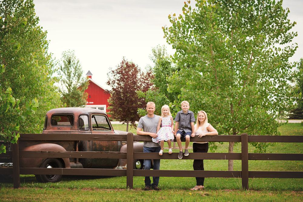 Family of 4 in front of the barn and old truck. Calgary Family Photographer. Milashka Photography