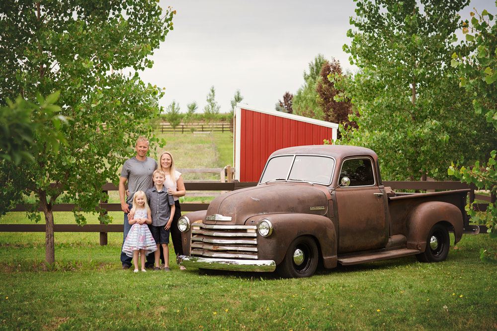 Family of 4 standing in front of an old truck. Calgary family photographer. Milashka Photography