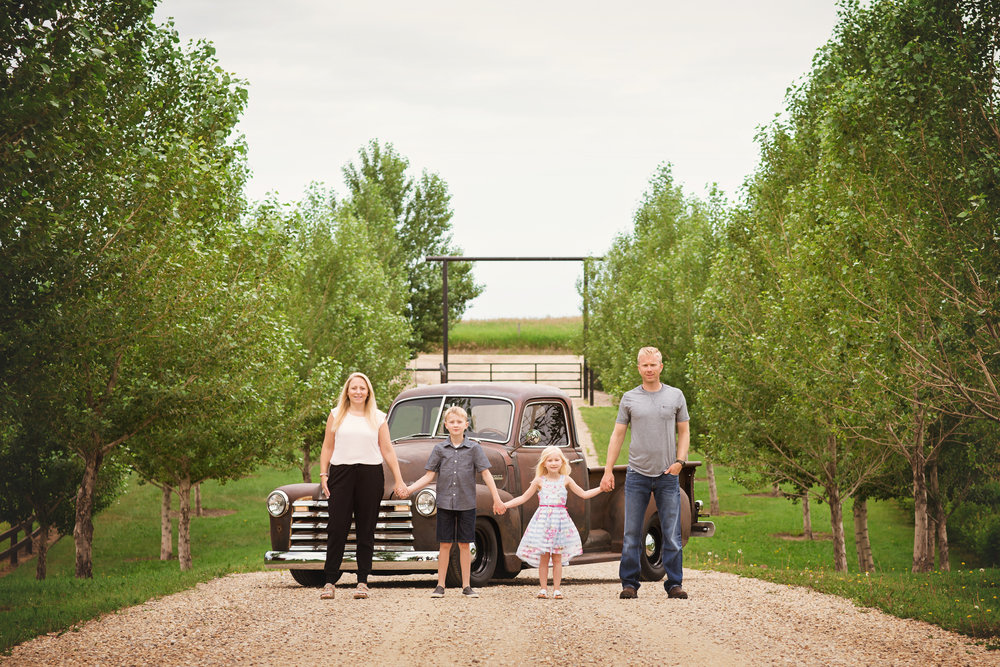 Family of 4 holding hands. Calgary family photographer. Milashka Photography