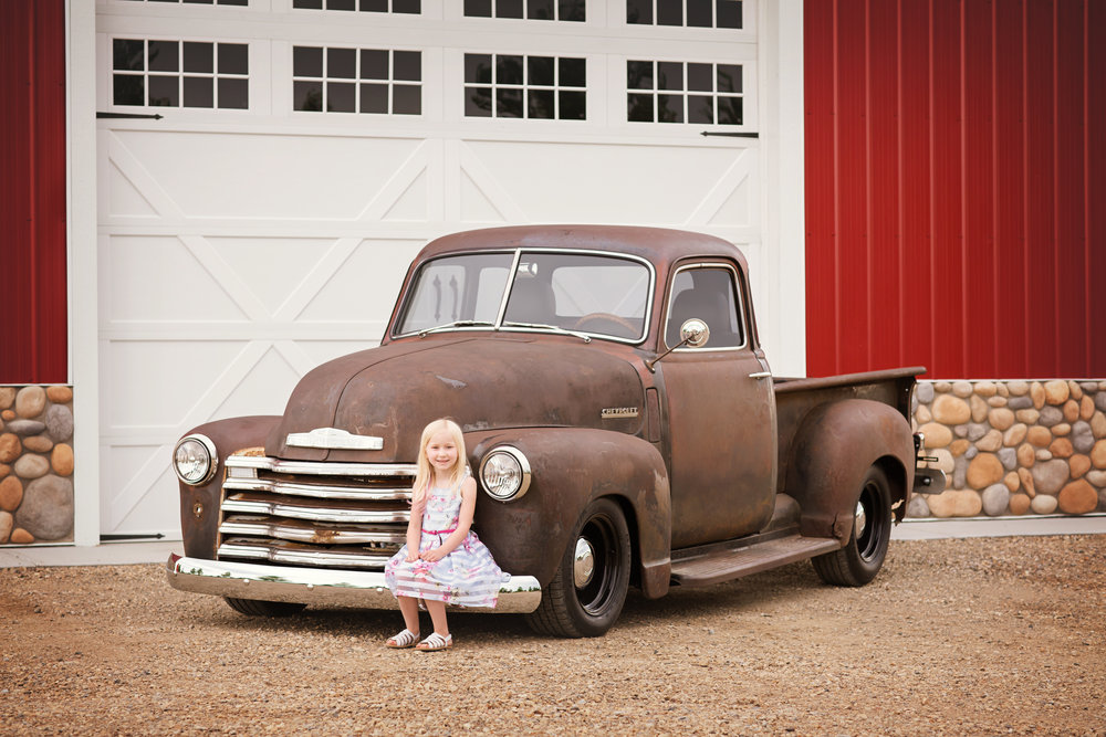A little girl sitting on the truck. Calgary family photographer. Milashka Photography.