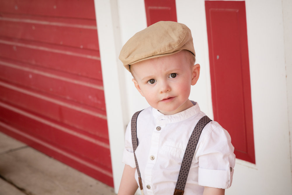 Little boy dressed in the old style clothing beside barn. Calgary child photographer. Milashka Photography.