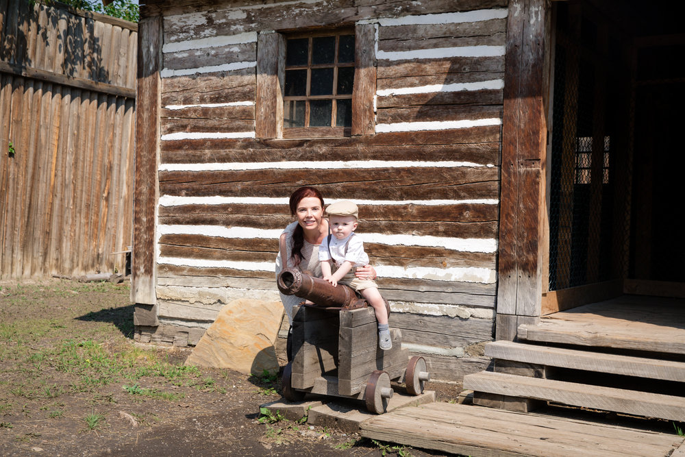 Mom and son. Little boy sitting on a cannon infant of an old house. Calgary photographer. Milashka Photography
