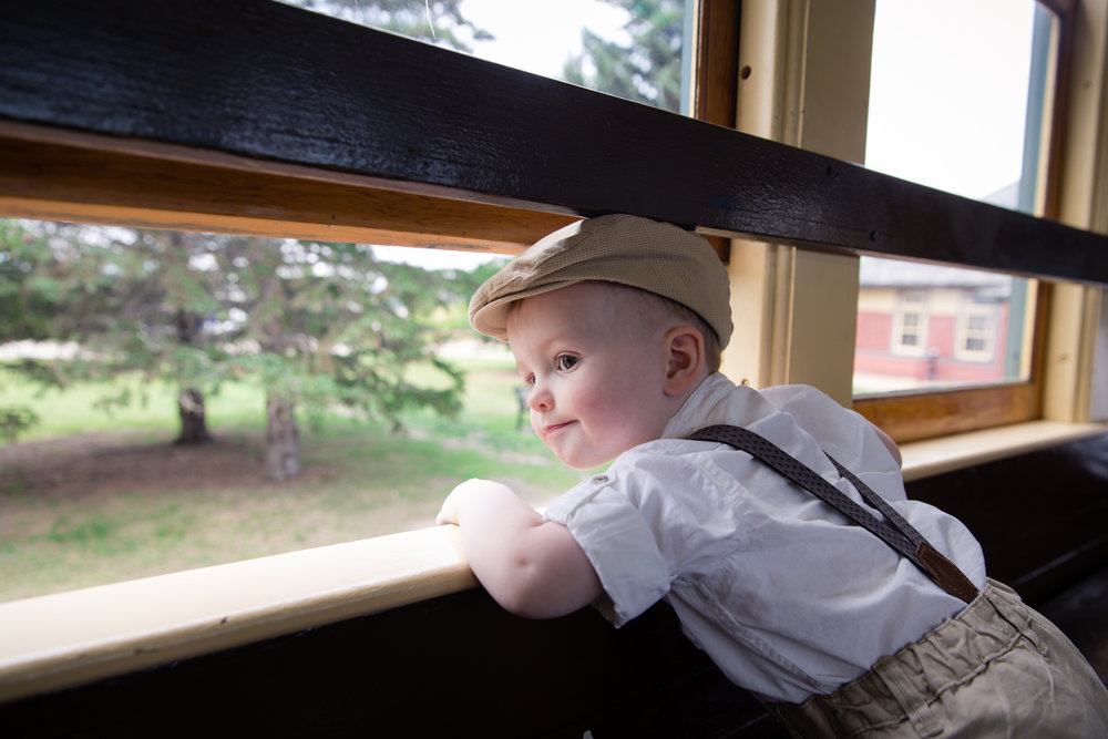 Sweet little boy looking at the window on a train at Heritage Park, Calgary, Alberta. Calgary family and child photographer. Milashka Photography