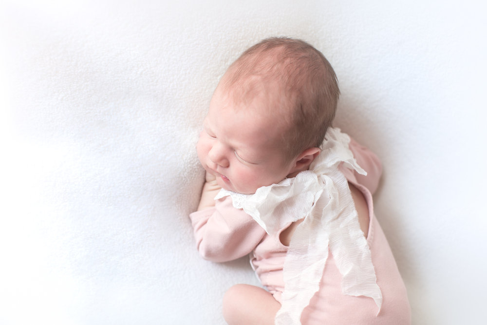 Beautiful newborn baby girl in a cute pink romper on a beanbag. Calgary Newborn photographer. Milashka Photography