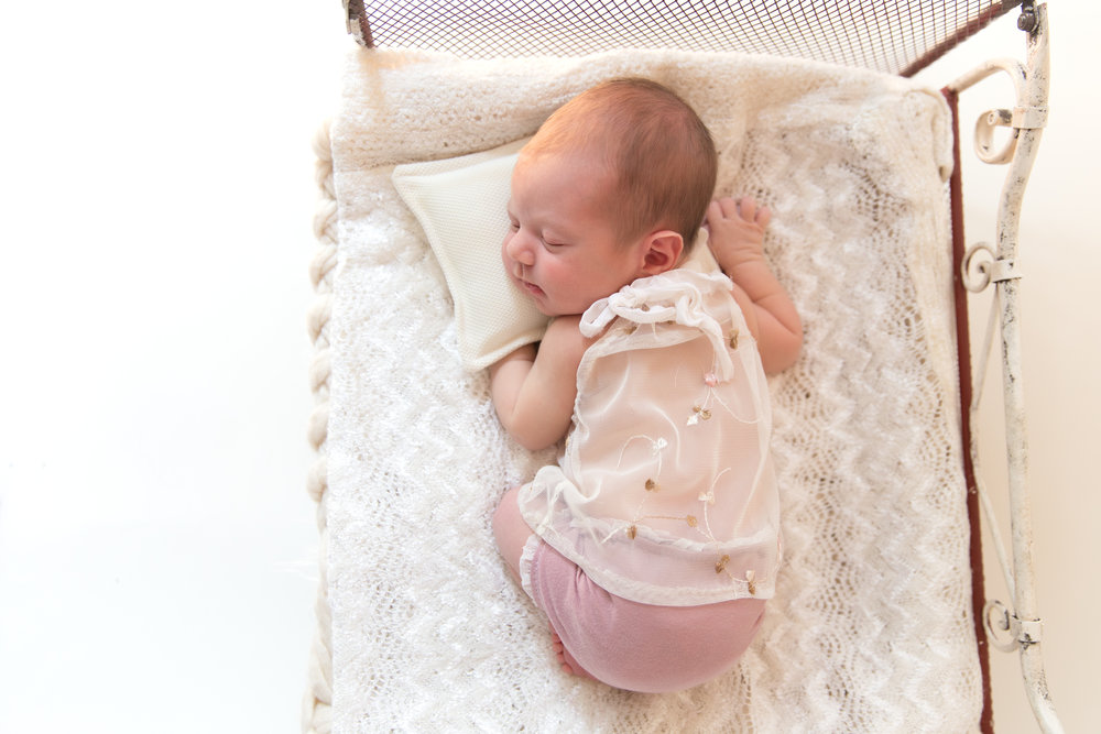 Beautiful newborn baby girl sleeping soundly on an antique bed. Calgary Newborn Photographer - Milashka Photography