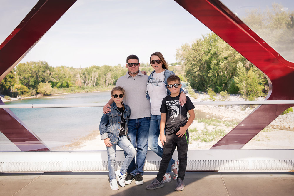 Family of 4 standing on a Peace Bridge in Calgary, Alberta. Calgary family photographer. Milashka Photography.