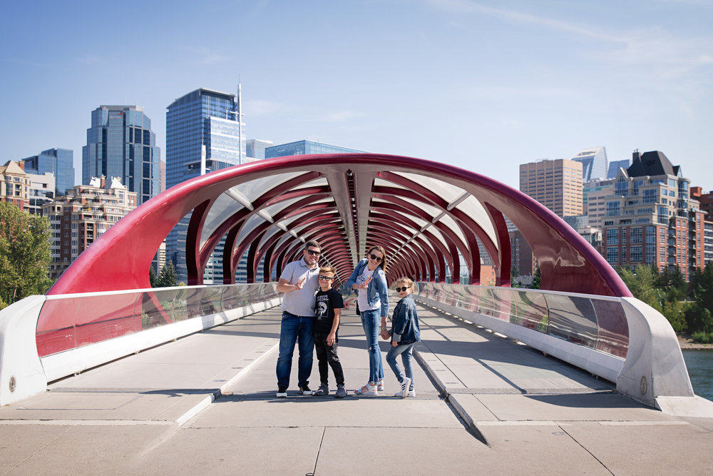 Family of 4 standing on a Peace Bridge in Calgary, Alberta, Canada. Calgary family photographer - Milashka Photography