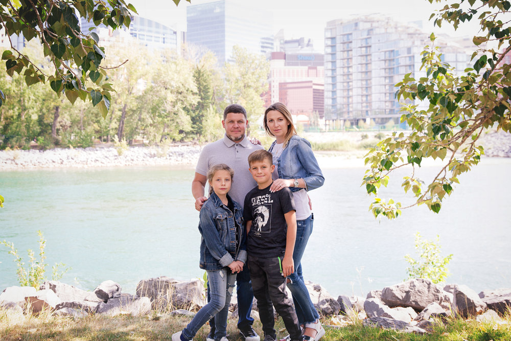 Family of 4 standing infront of the Bow River in Calgary downtown. Calgary family photographer. Milashka Photography