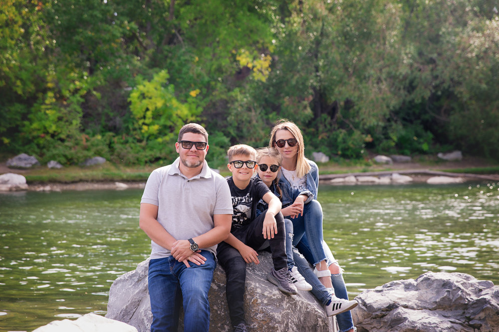 Family of 4 sitting on a rock and wearing sunglasses. Calgary Family photographer. Milashka Photography