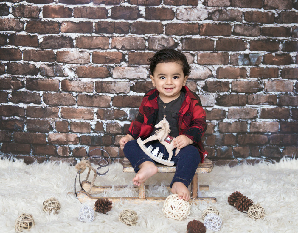 Happy 1 year old sitting on a sled and smiling for his Christmas inspired photoshoot