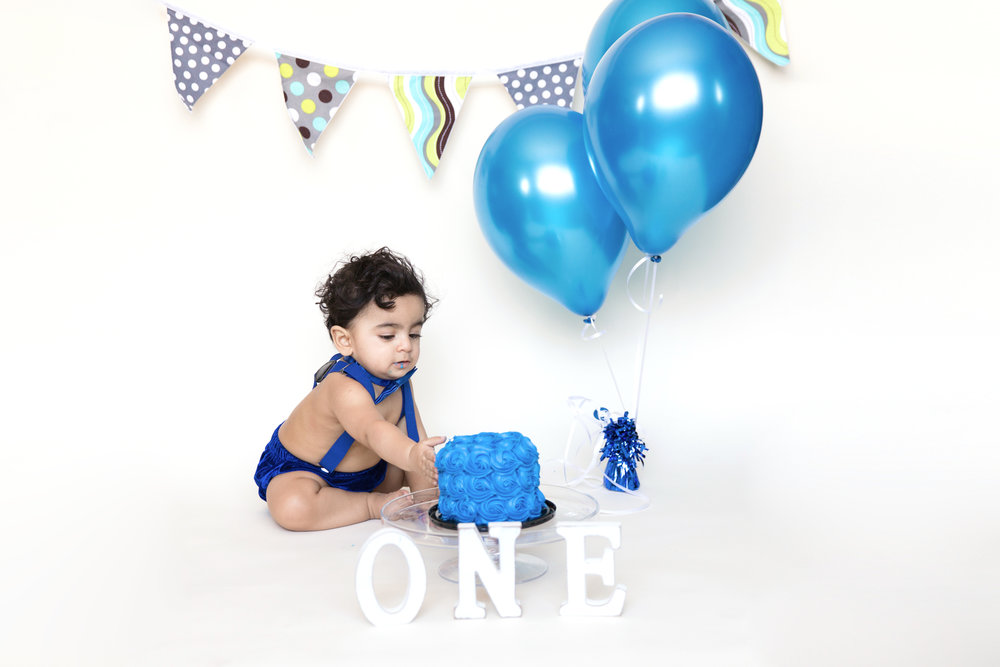 First Birthday photoshoot. Calgary Cakesmash Photographer. Baby boy is reaching for his birthday cake. Milashka photography