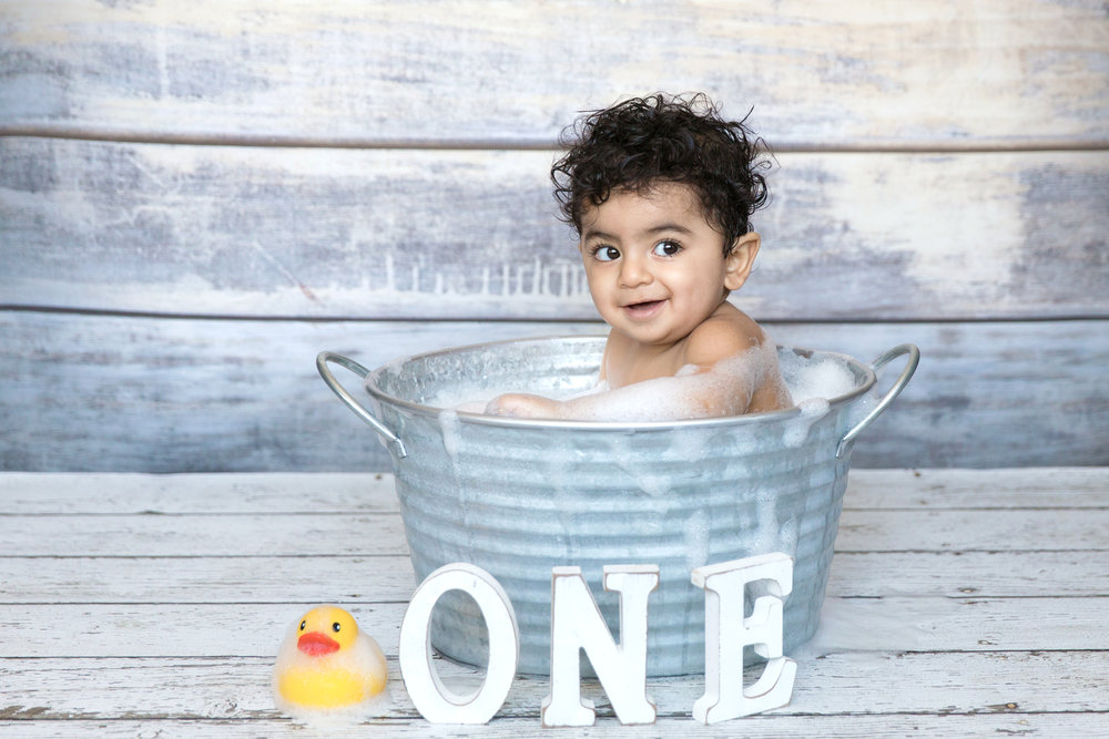 Baby boy is taking a bubble bath after smashing his cake during a cakesmash photoshoot. Calgary photographer. Milashka Photography