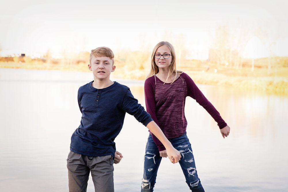 Brother and sister doing the Floss Dance. Family photographer. Calgary. Milashka Photography