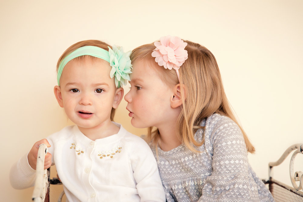 Sisters are telling secrets. A big sister is whispering a secret to her little sister's ear. Calgary child photographer. Milashka Photography