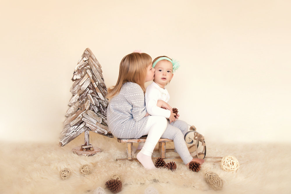 Big sister is kissing her little sister. Christmas inspired photoshoot. Neutrals. Calgary children photographer. Milashka Photography