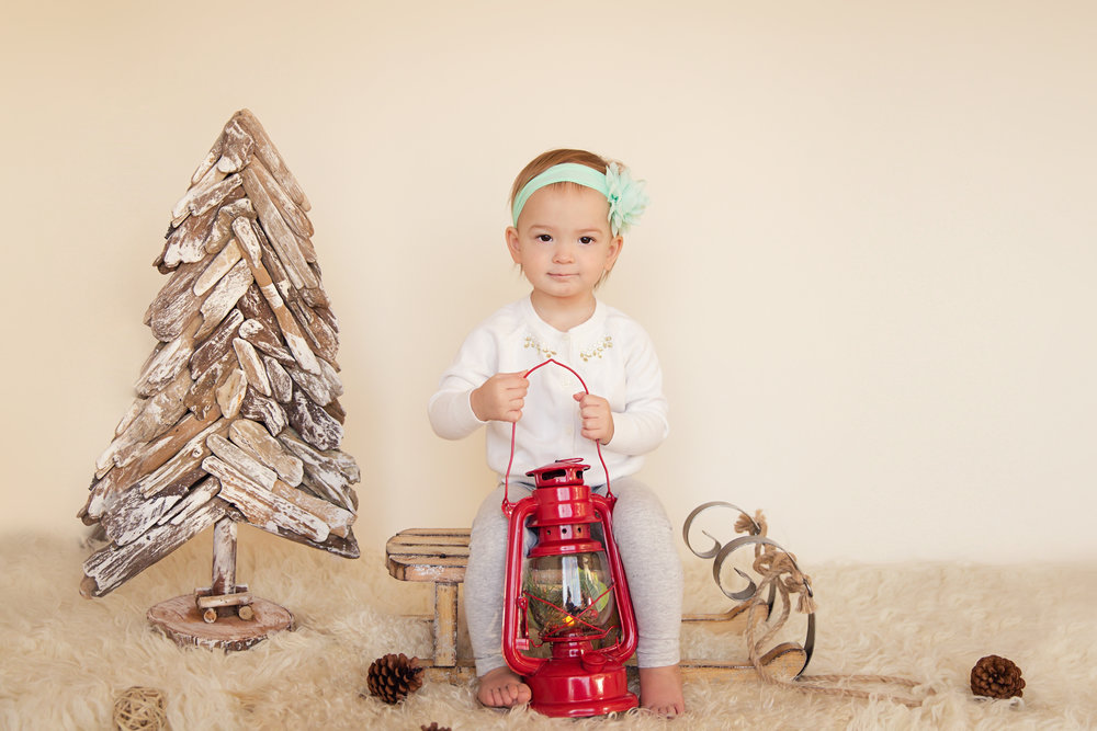 Little girls is holding her lantern in this Christmas inspired photo session. Calgary Child Photographer. Milashka Photography