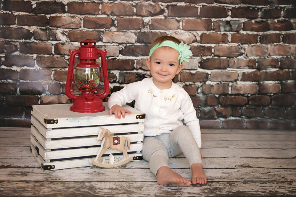 Little girl is smiling in this Christmas inspired photoshoot. Calgary child photographer. Milashka Photography