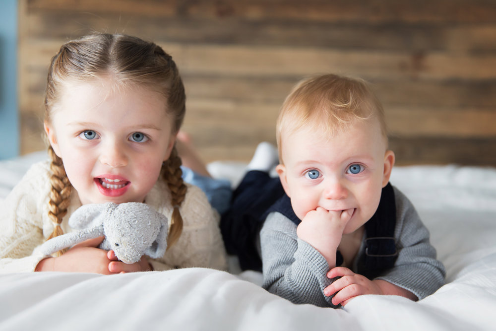 Sibling lying on the bed in this lifestyle inspired photoshoot. Calgary Family photographer. Milashka Photography