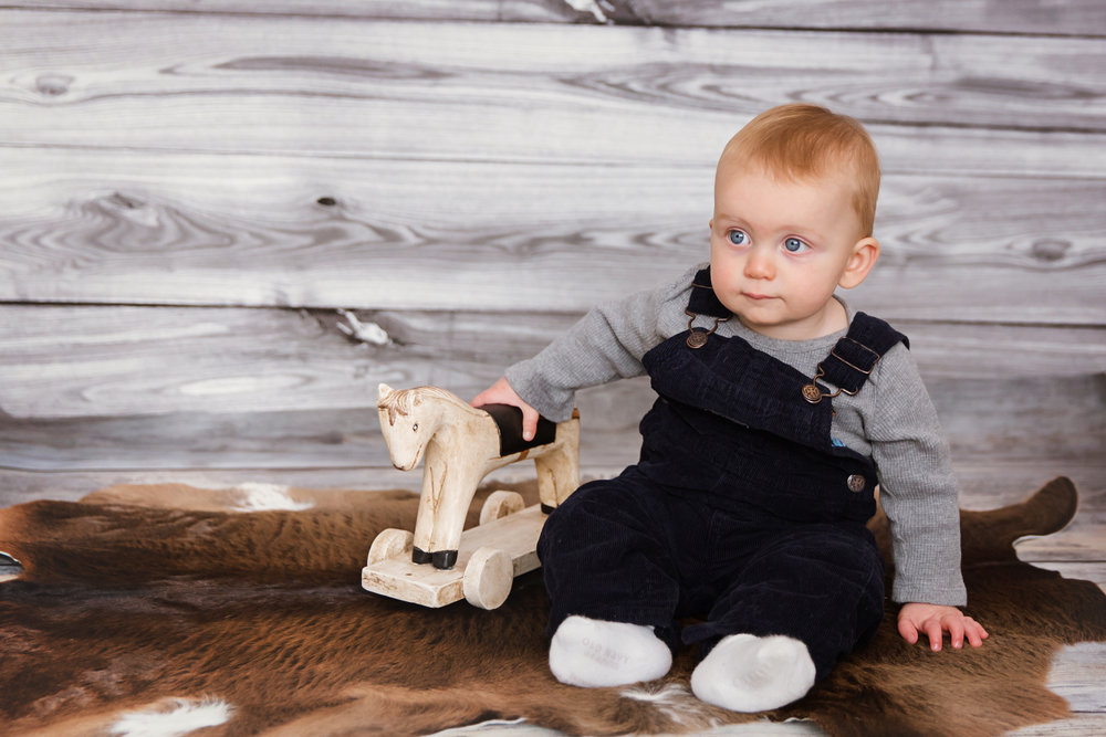 Baby boy is sitting and holding a wooden horse. Calgary baby photographer. Milashka Photography
