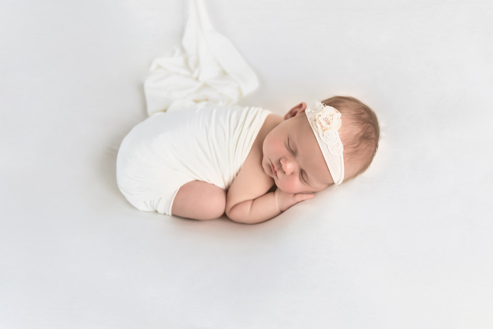 Bum up pose on a beanbag with white backdrop. Baby girl on a beanbag. Newborn photography. Calgary Photographer. Milashka Photography