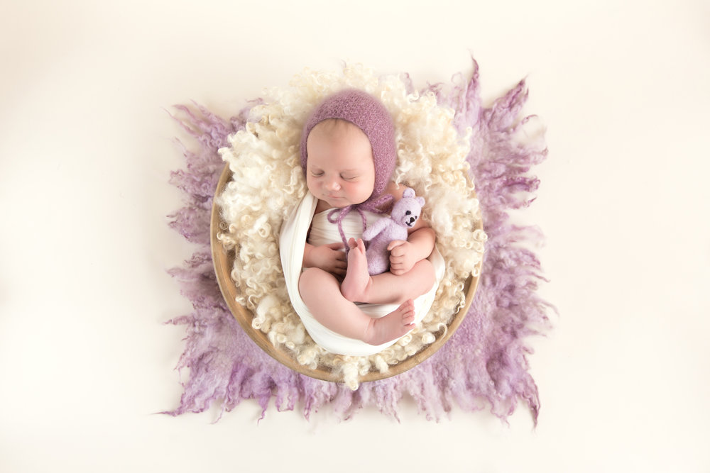 Baby girl in a wooden bowl wearing a lilac hat, holding a lilac bear and surrounded by lilac fluff. Calgary Newborn Photographer. Milashka Photography
