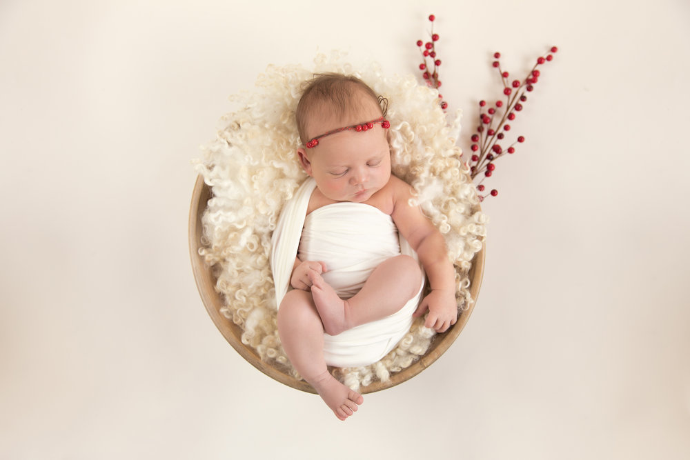 A simple Christmas inspired set up with a newborn baby girl in a bowl. Calgary Newborn Photographer. Milashka Photography