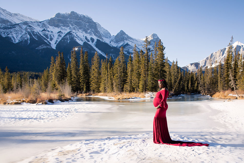 Beautiful expecting mother to be in a red gown on a snow with Rocky Mountains in the background. Calgary Maternity Photographer - Mountain Maternity Session in Alberta - Milashka Photography