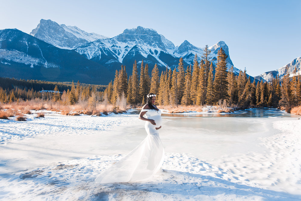 Beautiful mom-to-be in a gorgeous white gown standing on a snow with Rocky Mountains, river and forest in the background. Calgary Maternity Photographer - Mountain Maternity Session in Alberta - Milashka Photography.
