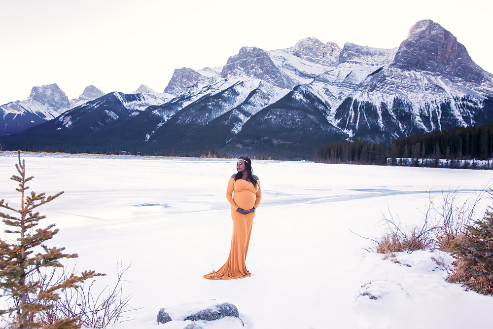 Proud mama to be in a gorgeous mustard gown standing in the snow surrounded by Rocky Mountains in beautiful Canmore, Canada. Calgary Maternity Photographer - Mountain Maternity Session in Alberta - Milashka Photography